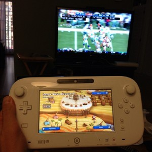 This is an image of a gentleman playing New Super Mario Bros. U on his Wii U gamepad while watching football on his TV. Woah!